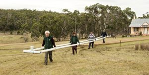 Bruce, Anne, Peter and Richard joyfully carrying drainage pipes to their new home.
