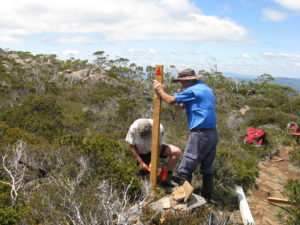 Two men installing a marker pole in the bush